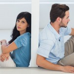 Sitting couple are separated by wall with woman looking at camer